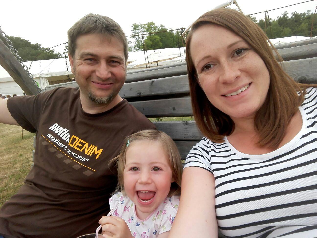 Christian Kugler mit Frau und Tochter beim Lächeln im Garten