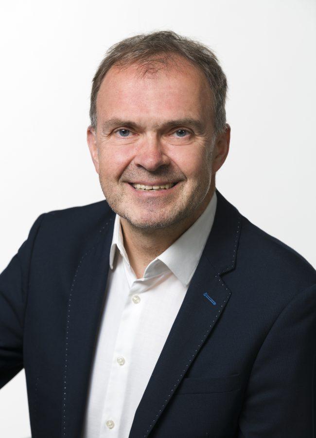 Roger Hackstock mit blauem Sakko und weißem Hemd