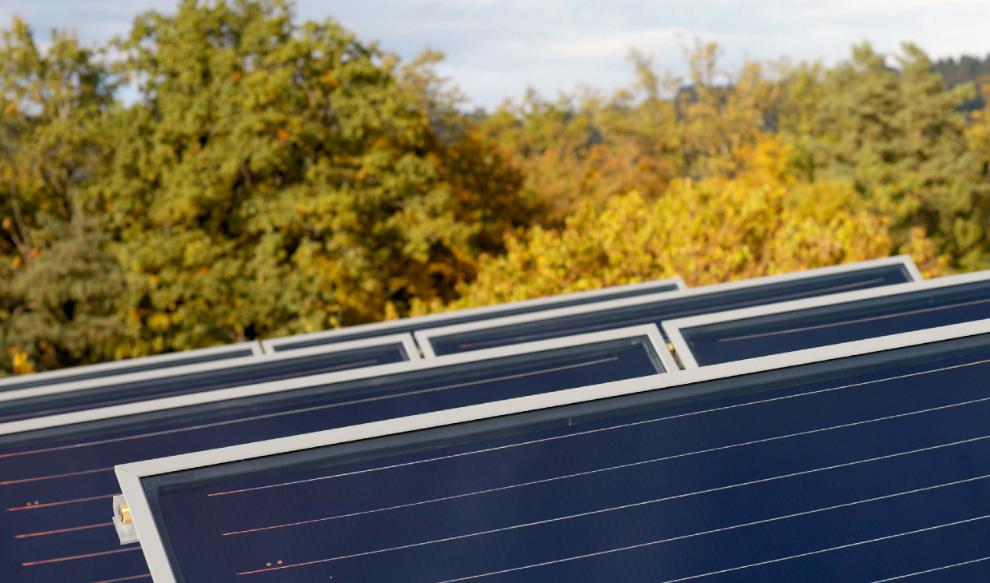 Nahaufnahme einer thermischen Solaranlage mit Bäumen im Hintergrund